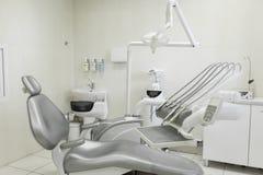 En modern brunn-utrustad arbetsplats för tandläkare` s, en tålmodig grå färgstol för ` s Maskin för att borra tand- tänder och an royaltyfria foton