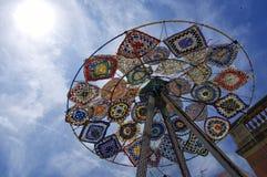 En modern färgrik skulpturinstallation som göras av använda paraplyer, fena, badskor som placeras i cente royaltyfri fotografi