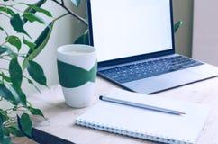 En modern kontorsarbetsplats som omges av gröna växter En trätabell med en bärbar dator, en anteckningsbok, en blyertspenna och e Arkivfoton