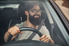 En modern skäggig man som kör en bil fotografering för bildbyråer