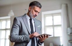 En mogen affärsman som står i ett kontor, genom att använda minnestavlan arkivfoton