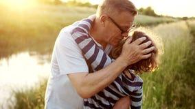 En mogen man kramar, slår huvudet, kysser hans sena barn Älskvärd lockig pojke Familjferie i natur lycklig familj stock video