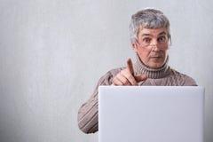 En mogen man med bärande exponeringsglas för grått hår som placerar på tabellen som arbetar med hans bärbar dator som skriver någ Arkivfoto
