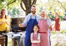 En mogen man med familjen och vänner som lagar mat mat på ett grillfestparti royaltyfri foto
