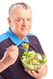 En mogen man som äter sallad Royaltyfri Fotografi