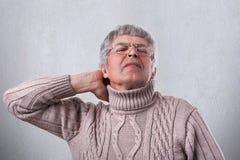 En mogen man som bär den varma tröjan och glasögon som rymmer hans hand på halsen som tröttas efter arbete i trädgården Ett trött royaltyfri fotografi