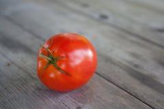En mogen röd tomat på den gamla trätabellen Arkivfoto