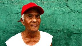 En mognad filippinsk man står mot en grön vägg royaltyfria bilder