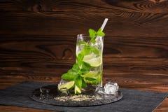En mojitococtail med ett sugrör på en träbakgrund Grön mintkaramell och ny limefruktmojito Uppfriskande alkoholdrinkar kopiera av Arkivbilder
