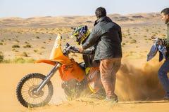 En mopedryttare snurrar upp sand i Sahara Desert royaltyfria bilder