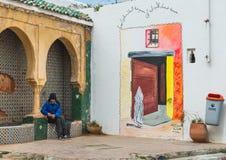 En moroccan gamal man sitter nära den färgglade målningen Royaltyfri Foto