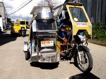 En motorcykel som är inpassad med extra hjul och en taxi vänds in i vad kallas en trehjuling Royaltyfria Foton