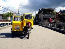 En motorcykel som är inpassad med extra hjul och en taxi vänds in i vad kallas en trehjuling Arkivbild