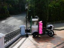 En motorcykel som skräddarsy för att sälja den rosa sockervadden på hjärtförmaken av en katolsk kyrka royaltyfri fotografi