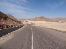 En motorcyklist rider på en bergväg royaltyfri bild