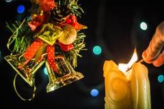 En mousserande stearinljus tänder en hand med en match Nära filialerna av julgranen med klockor royaltyfri foto