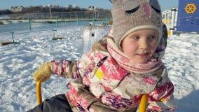 En muchacha del parque del invierno en un oscilación almacen de metraje de vídeo
