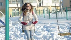 En muchacha del parque del invierno en un oscilación almacen de video