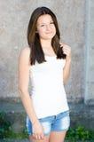En muchacha sonriente y de mirada feliz joven de la cámara que se coloca en el copyspace gris del fondo de la pared Fotografía de archivo libre de regalías
