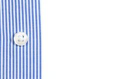 En muff av en blå randig skjorta med en knapp på den vita bakgrunden Arkivbilder