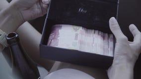 En mujer caucásica del coche los controles abren la pequeña caja negra con moneda extranjera almacen de video