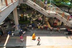 En munk bland andra gångare förbigår stallsna i Victory Monument i Bangkok, Thailand arkivbilder