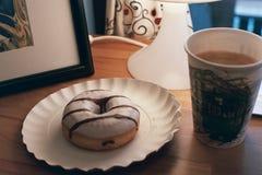 En munk och ett kaffe i ett bergkafé arkivfoto