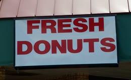 En munk shoppar annonserar nya varma donuts royaltyfri fotografi