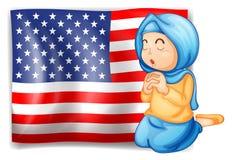 En muselman som framme ber av USA flaggan Royaltyfri Foto