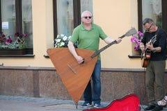 En musikalisk grupp av tre personer p? en gammal europeisk gata Musikbandet best?r av tv? m?n och en flicka M?n med en basfiol oc arkivbilder