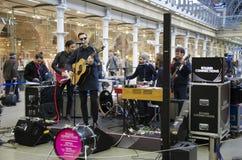 En musikband som namnges 'Gaspard Royant', utför en uppsättning på St Pancras den internationella stationen Royaltyfria Foton