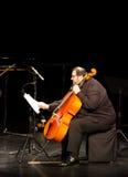En musiker av den Hasmik Leyloyan gruppen plays violoncellen Arkivbild