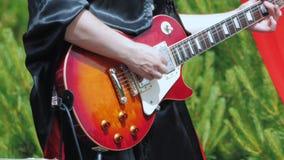 En musiker i svart gotisk kläder spelar den elektriska gitarren arkivfilmer