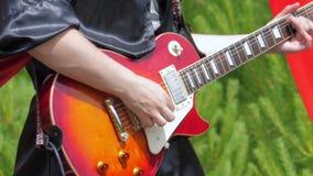 En musiker i svart gotisk kläder spelar den elektriska gitarren lager videofilmer