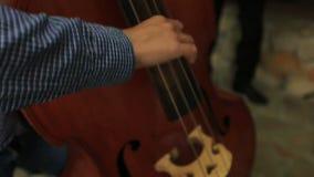 En musiker som spelar nära övre för kontrabas lager videofilmer