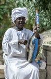 En musiker spelar en egyptisk gitarr för turister på Philae i Egypten Royaltyfri Bild