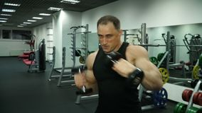 En muskulös boxare med hantlar i hans hand utarbetar slag lager videofilmer