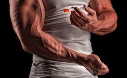 En muskulös man med en injektionsspruta arkivfoto