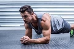 En muskulös man på plankaposition arkivfoto