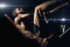 En muskulös man utför övningar på sportar som utbildar apparaturen för benmuskler i en mörk idrottshall som lyfter vikter arkivbild