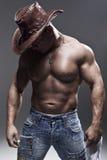 En muskulös man i en cowboyhatt Arkivbild