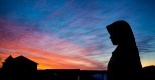 En muslimsk kvinna som ser ut ur hennes lägenhet royaltyfri bild