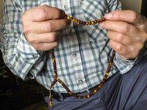 En muslimsk man, som tilldrar beröm, en muselman som tillber en muslimsk man som drar en radband Royaltyfria Bilder