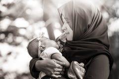 En muslimsk moder med henne behandla som ett barn Arkivbild