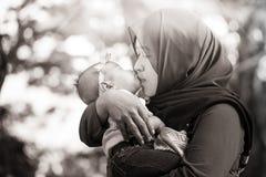 En muslimsk moder med henne behandla som ett barn Royaltyfri Bild