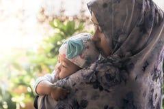 En muslimsk moder som rymmer henne, behandla som ett barn dottern Royaltyfri Foto