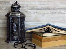 En mycket gammal silverlykta, en hög av gamla böcker, ett par av exponeringsglas på blekt ekbakgrund royaltyfria bilder