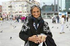 En mycket gammal turkisk kvinna som säljer fågelfrön Arkivfoton