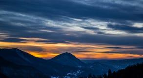 En mycket intressant solnedgång Sikt från ovannämnt på kullarna i avståndet Den blåa och gula färgen av himlen i bakgrunden royaltyfria bilder