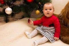 En mycket liten flicka sitter under en julgran med färgrika garneringar nytt treeår för jul fotografering för bildbyråer